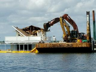 Sinking houseboat being demolished