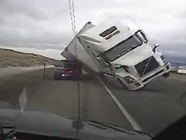 Wind gust blows semi on top of police vehicle