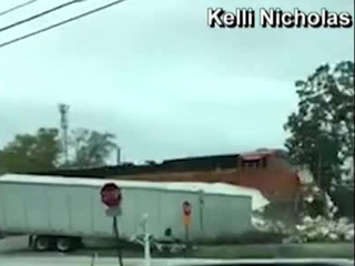VIDEO: Train strikes semi carrying candy