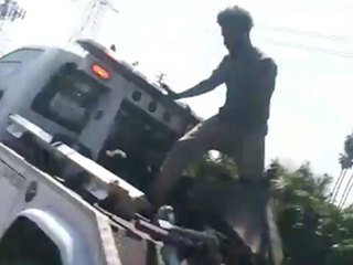 Wild ride: Man jumps onto tow truck to free car